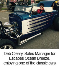 Deb Cleary, Sales Manager for Escapes Ocean Breeze, enjoying one of the classic cars